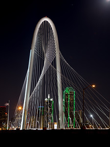 Dallas skyline behind Margaret Hunt Hill Bridge with moon peaking out.