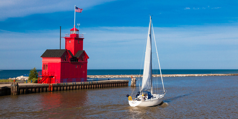 A sailboat passes by the Holland Lighthouse on its way to Lake Michigan. Holland, MI<br /> <br /> MI-090627-0037