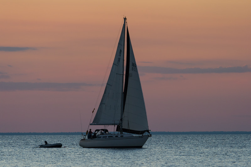 A sailboat returns to port at the end of a summer day. Door County, WI<br /> <br /> WI-080830-0181