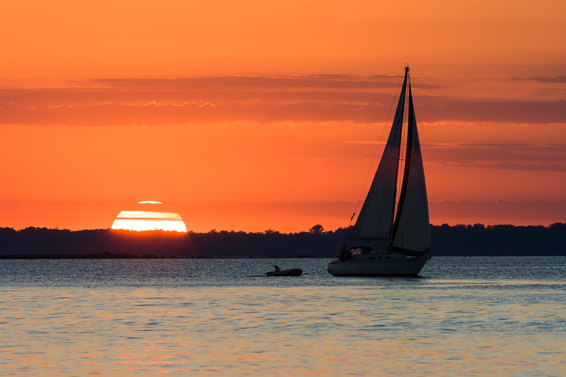 The sun sets over the Green Bay waters as a sailboat passes by. Door County, WI<br /> <br /> WI-080830-0170