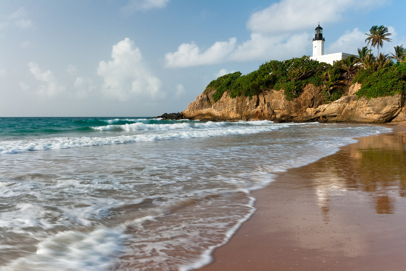 The reflection of the Manuabo Lighthouse can be seen on the remnants of the surf. Maunabo, PR<br /> <br /> PR-070727-0014