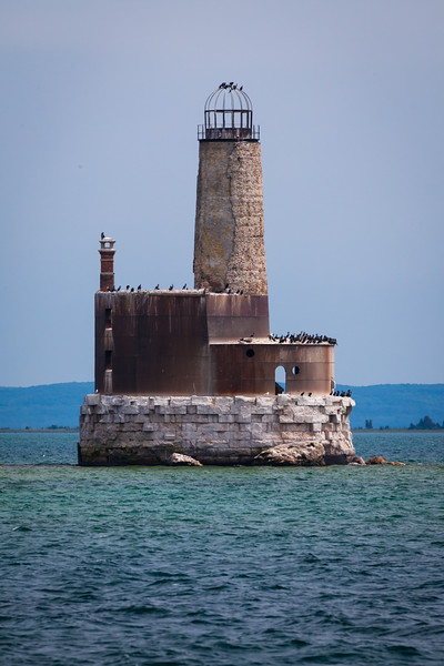 Waugoshance Shoal Light was constructed in 1851 to mark the shoals extending from Waugoshance  Point. It was built of brick and in 1883, sheathed with 3/8-inch thick steel. The light was decommisioned in 1912 and in the early 1940s  became a target for practice bombing. Today it stands without some of the metal casing deteriorating and serving as a bird colony. There are efforts underway to stabilize and possibly restore the light. Note that one can see straight through the interior of the lighthouse. Straits of Mackinac, MI<br /> <br /> MI-110707-0338