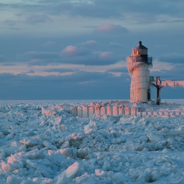 Sunset light warms the frozen channel and pierhead light at St. Joseph, MI<br /> <br /> MI-090125-0171