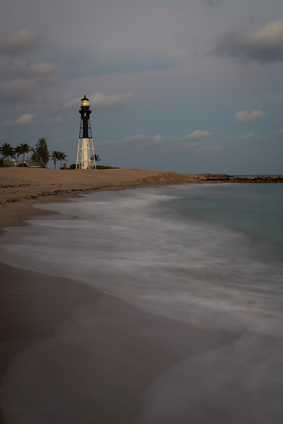 The light of the Hillsboro Inlet lighthouse shines at dusk on a warm late December evening. Pompano Beach, FL<br /> <br /> FL-121226-0025