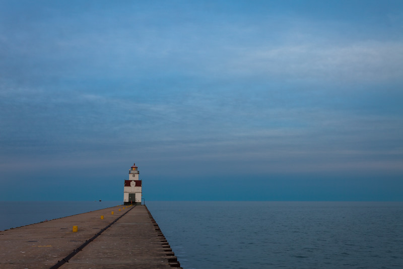 The blue water and sky contrast with warm sun glow reflected on the light tower of the Kewaunee lighthouse. Kewaunee, WI<br /> <br /> WI-100515-0277