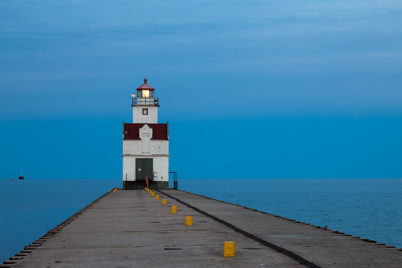 The blue water and sky contrast with warm sun glow reflected on the light tower of the Kewaunee lighthouse. Kewaunee, WI<br /> <br /> WI-100515-0284