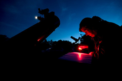 "Amy Cantu of Ann Arbor looks at a star chart next to her 8"" telescope at Peach Mountain near Dexter, Michigan in June of 2010."