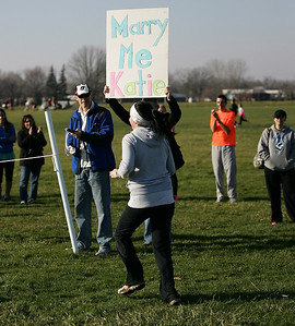Katie Knight reaches the finish line where Ted Wallingford proposes marriage with a sign. Race timer Doug Herndon is next to the sign. photo by Ray Riedel
