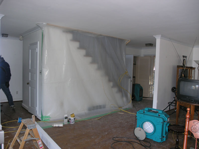 Picture of the stairway from the living room. The power and water have been shut off. Temporary power lines (yellow cables in photo) are powering base heaters, blowers, and work lights. The stairwell has been covered in plastic sheeting to keep the heat downstairs.