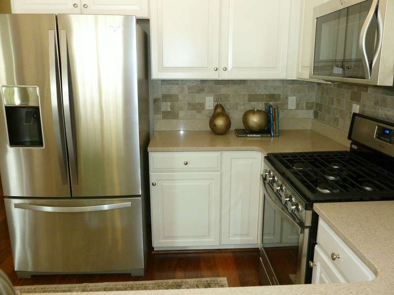 Frig will be side by side, not with freezer on bottom.  Wood-finish cabinets and dark Ubatuba granite counters.  Lazy susan cabinets in corners.  Stainless appliances.