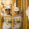 Fig 7.26 / Volunteers building a house / Habitat for Humanity<br /> <br /> Choice  13 of 13<br /> <br /> Two Hispanic teen female volunteers smile while standing in between support beams of house frame being built by Habitat For Humanity in Long Beach, CA