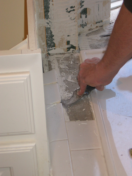 Tony chips away at the jacuzzi surround tiles.