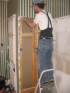 Tony stripping the shower wall down to the studs.