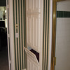 Before: The wallpaper is dated and the laundry hamper door mechanism is broken.