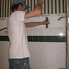 The shower's tile and cement board backing reluctantly yield to Tony's hammer and chisel.