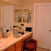 """Wendy's vanity before. Wendy has always been unsatisfied with the standard, boring, 3"""" white square tile on the countertops, shower walls and around the tub. That's the door to the closet. Notice the huge mirror."""