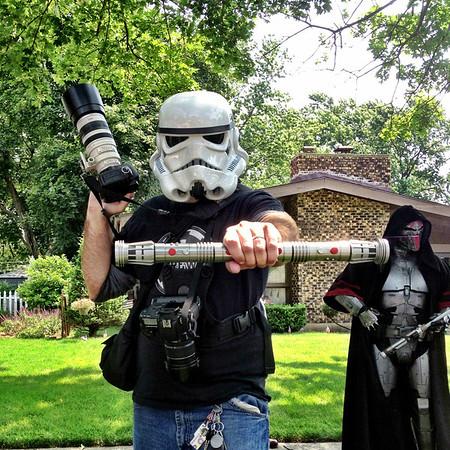 Matthew in Stormtrooper helmet, with lightsaber and blaster (Canon)