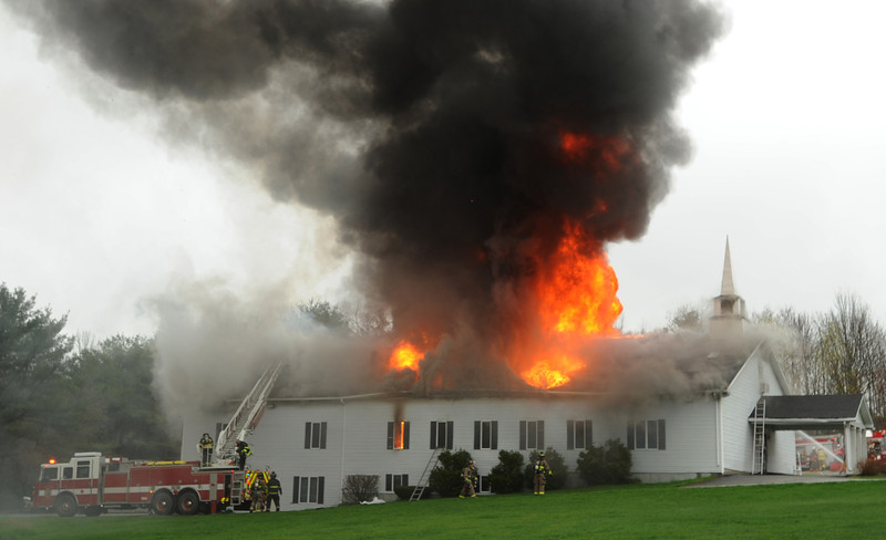 CAPTION<br /> The Calvary Apostolic Church in Winterport is seen in flames as fire fighters collect equipment and pull back when the roof collapsed on Thursday, May 5, 2011. One person is confirmed dead due to the blaze. BDN Photo by Kevin Bennett   (WEB EDITION PHOTO)