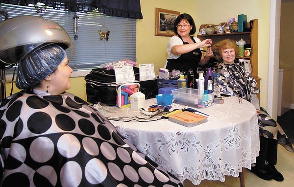Kristi Caples, center, trims Janice Gaunt's hair as friend Shirley Popplewell sits under the hair dryer.  Caples operates Hair I Am, a mobile hair care service.