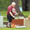 Donald Riggs, of Anderson, decorates his parents grave in Maplewood Cemetery Monday for Memorial Day.