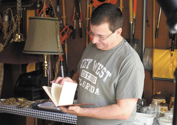 Robert Banz checks out a book for sale at his neighbors garage sale as the residents of Pendle Hill prepare for their annual neighborhood garage sale.