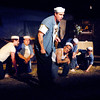 "Seabee Luther Billis (Andrew Persinger) leads his fellow sailors in song in the Mainstage production of the musical ""South Pacific."""