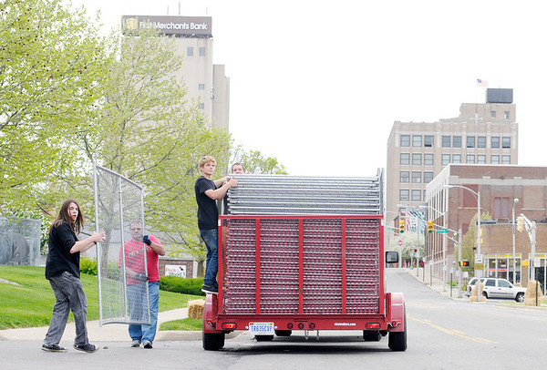 From left, Tyler Baugher and Steve Branch move a section of fence into place as Christian Busnelli and Dalton Strunk wait to off load the next piece of fencing as volunteers set up the track for the 19th Annual Sertoma Club Mayor's Cup Grand Prix Go Kart Race on Friday. Racing starts at noon downtown on Saturday.