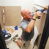 Work is being done on remodeling a suite in the Union Building for the Madison County Chamber.  Here  Pat Corn of Midwest Luxury Bath works as they are totally remodeling one of the restrooms in the suite.
