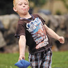 James Malone, 8, puts some body english on his toss as he plays cornhole at Shadyside Park Monday during a family holiday picnic.<br /> To purchase this photo or other photos produced by The Herald Bulletin<br /> staff, visit heraldbulletin.smugmug.com.