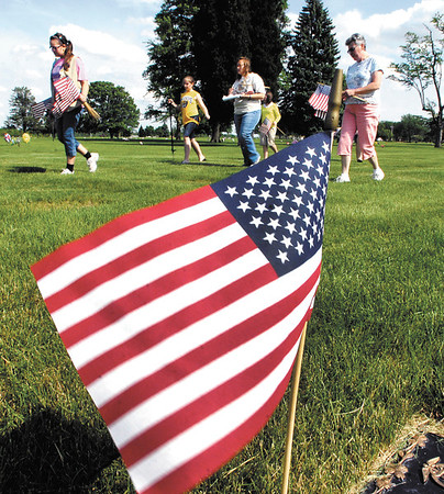 With a list of veterans buried in Anderson Memorial Park Cemetery grouped by area the Girl Scouts walk down each row of markers finding the names then placing an American flag at the grave.