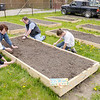 Tony and Sarah New and Mason and Emily Jarvis plant and decorate the family's plot in the Community garden at the Anderson Impact Center on Saturday.
