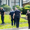 Officers search the area of a shooting on Nichol Avenue just east of Arrow Avenue on Wednesday afternoon.