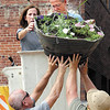 First Lady Anita Smith and Parks Department employee Ranny Hinton take a  flower basket into their bucket as part of a city Beautification program kicked off by Smith Monday afternoon.  They then ceremoniously hung the last flower basket along Meridian Street in downtown Anderson.