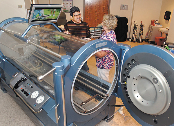 Bob Garcia and registered nurse Bobbi Eads, clinical manager of the Wound Center, are shown at the center, next to one of the hyperbaric chambers where Garcia was treated.