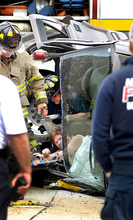 Anderson Fire Department personnel work to free this woman from her SUV that had rolled after being involved in a 2-vehicle crash Saturday afternoon at 13th and Jackson Street.