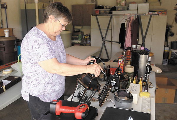Ruby Marling looks at light fixtures for sale at her neighbors garage sale as the residents of Pendle Hill prepare for their annual neighborhood garage sale.
