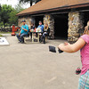 Briley Malone, 9, right foreground, tosses her bean bag as she plays cornhole with her brother James, 8, as other family and friends watch during their family picnic Monday at Shadyside Park.