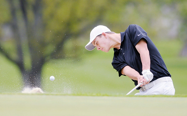Pendleton Heights' Colin Proctor hits out of the bunker on the eighth hole at Edgewood during the Madison County golf tournament on Saturday.