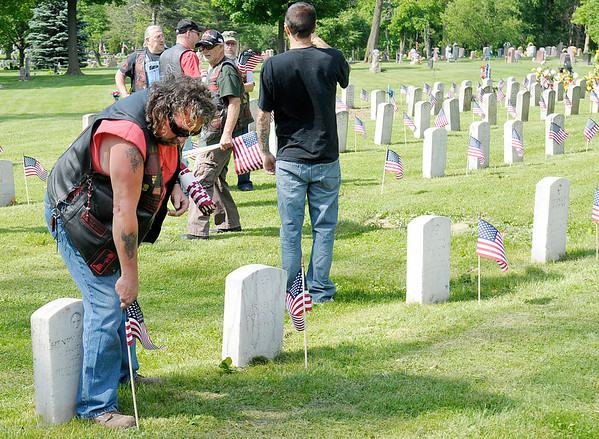 """Tim """"Shovel Head"""" Couch puts an American Flag on a veterans grave at Maplewood Cemetery on Wednesday. Couch is a supporter of the Vietnam Veterans Motorcycle Club of Anderson. For the last several years the club has volunteered to put the flags on veterans graves at Maplewood."""