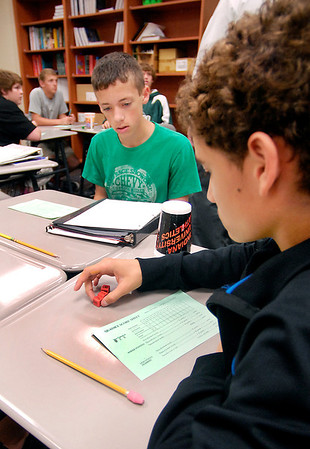 Pendleton Middle School 8th Grader Jackson Schlegelmilch, right, checks his numbers on the dice as he plays a math game with Jacob Noel in Sue Whitlow's pre-algebra class Wednesday.   The Pendleton Middle School was just named a 4-star school.