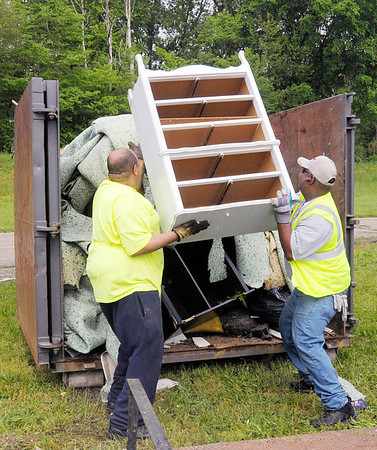 From left, Thomas Caldwell with Man 4 Man Ministries and Jeffery Davis with Anderson Light and Power toss a dresser into a dumpster during the 28th Annual J.T. Menifee City-wide Cleanup on Saturday.