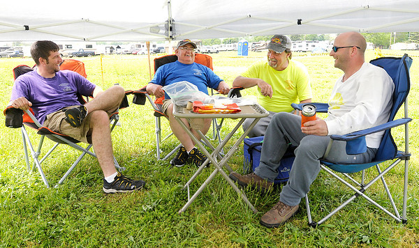 With the roof of their canopy lowered to keep out the rain, from left, Keith Krebs, Terry Krebs, Frank Ferry Jr. and J.T. Turner sit at their campsite at the  Anderson Speedway.