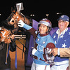 Bolt the Duer gets a pet from his driver Sam widger as winning trainer Peter Foley looks on as Bolt the Duer won the 20th running of the Dan Patch Invitational Saturday at Hoosier Park.