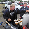 Greg Flora puts the finishing touches on the burgers as Ed Wells looks on with anticipation as they tailgate before the start of the Little 500 Saturday evening.  They came from Kokomo for the race.