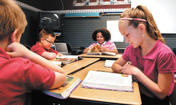 Jaden Dobbs, Ben Engle, Emma Coots, and Jada Mullins, third graders at Valley Grove Elementary School, read their favorite stories out of their reading book in Andy Raper's  class.  Valley Grove posted the highest pass rate within ACS in the IREAD testing.