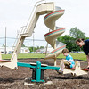 Devon Curl plays with his children Tesla, 2, and Emery, 7, on the teeter totter at Shadyside park during a break in the rain on Friday. More rain is forecast for Madison County on Saturday.