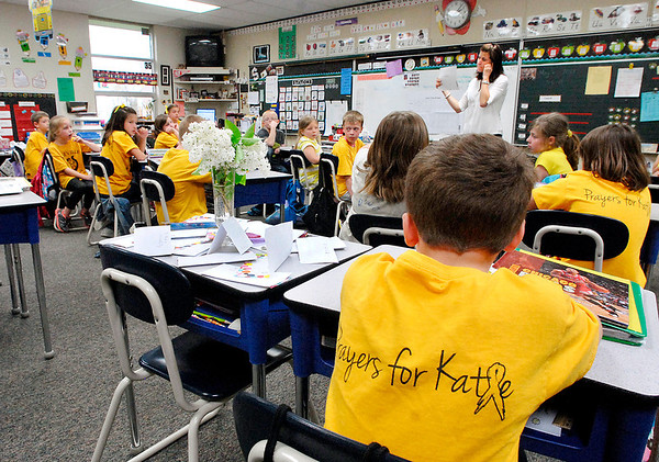 Daleville Elementary School 2nd grade teacher Amy Scheib conducts class as most of her students wear their Prayers for Katie t-shirts Monday.  Katie Kline was a student in the class and had passed away from cancer this past weekend.  Katie's desk sits empty except for the cards and flowers from her classmates.