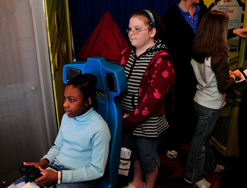 Debra, 10, watches as Chyanne, 11 plays the roller coaster video game.