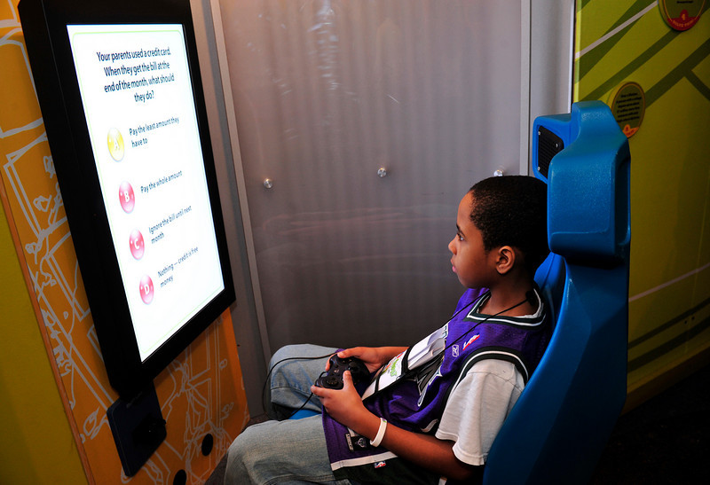 Bryson, 10 plays a roller coaster video game that asks financial questions.