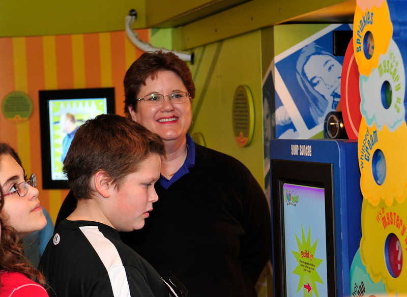 Luke, 11, plays with a game on the money bus as Julie, 10 watches.